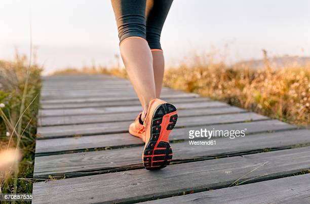 spain, aviles, young athlete woman running along a coastal path at sunset - orange shoe stock photos and pictures