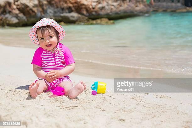 Spain, Baleares, Mallorca, baby girl playing on sandy beach