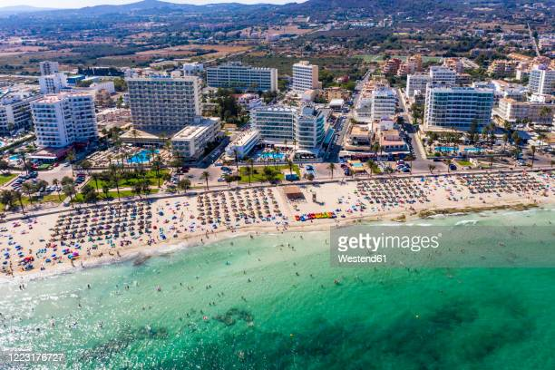 spain, balearic islands, cala bona, aerial view of resort town and crowded beach in summer - majorca stock pictures, royalty-free photos & images