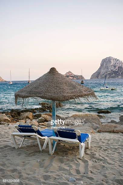Spain, Balearic Islands, Ibiza, Cala Es Vedra, sunbeds with sunshade in the evening light