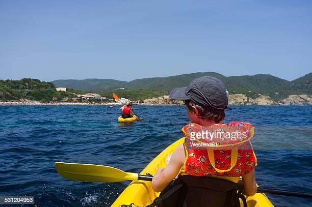 Spain, Balearic Islands, Ibiza, Es Figueral, young boy sitting in a kayak