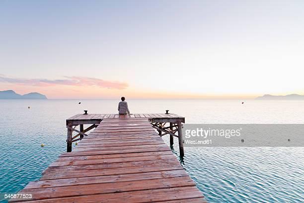 Spain, Balearic Islands, Majorca, one teenage boy sitting on a jetty in the morning