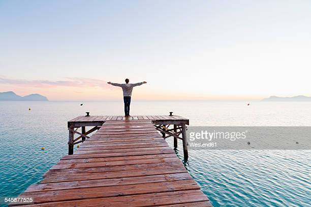 Spain, Balearic Islands, Majorca, one teenage boy standing on a jetty in the morning