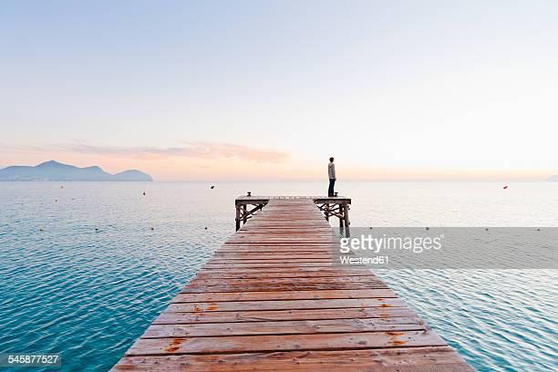Spain, Balearic Islands, Majorca, one teenage boy standing on jetty in the morning