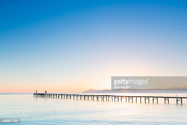 Spain, Balearic Islands, Majorca, people on a jetty at sunrise
