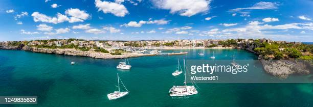 spain, balearic islands, mallorca, porto cristo, panorama of yachts sailing near coast in summer - manacor stock pictures, royalty-free photos & images