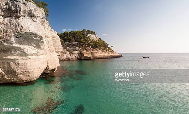 spain, balearic islands, menorca, cala mitjana, coast and boat - bucht stock-fotos und bilder