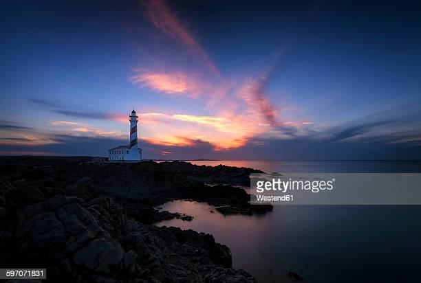 spain, balearic islands, menorca, faro de favaritx, lighthouse at sunset - faro stock photos and pictures