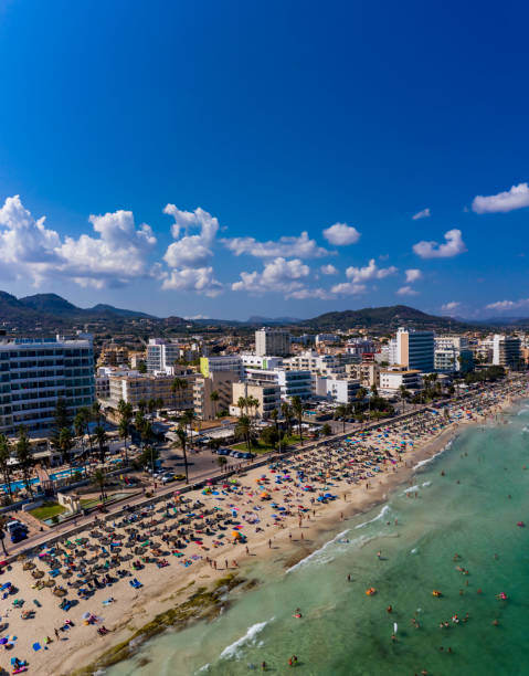 Spain, Balearic Islands,CalaBona, Aerial view of sky over resort town and crowded beach in summer