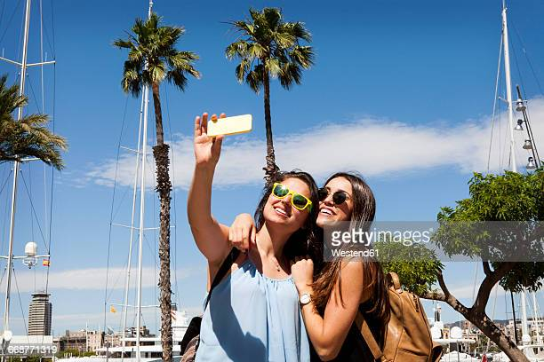 Spain, Barcelomna, two best friends taking selfie with smartphone
