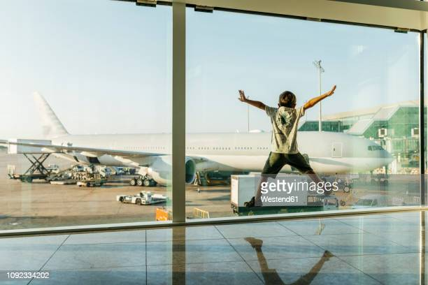 spain, barcelona airport, boy in departure area, jumping in front of glass pane - toddler at airport stock pictures, royalty-free photos & images