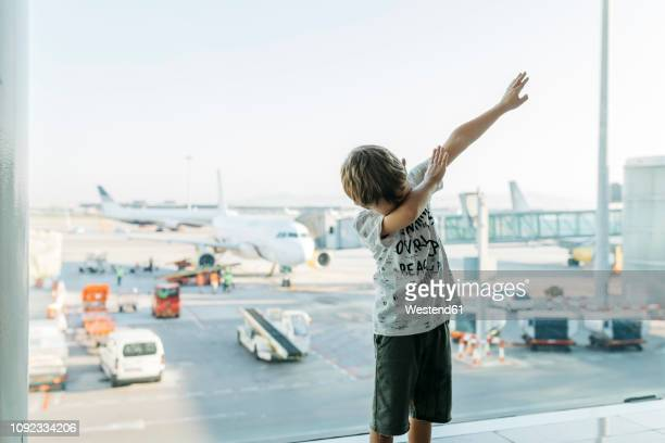 Spain, Barcelona airport, Boy in departure area, pretending to fly