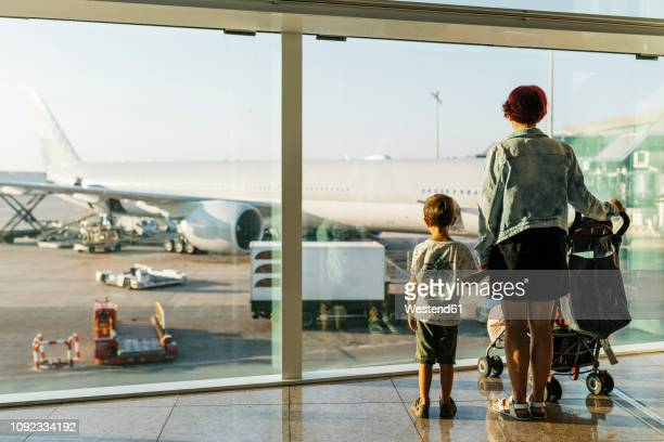 spain, barcelona airport, mother and son waiting in departure area - toddler at airport stock pictures, royalty-free photos & images