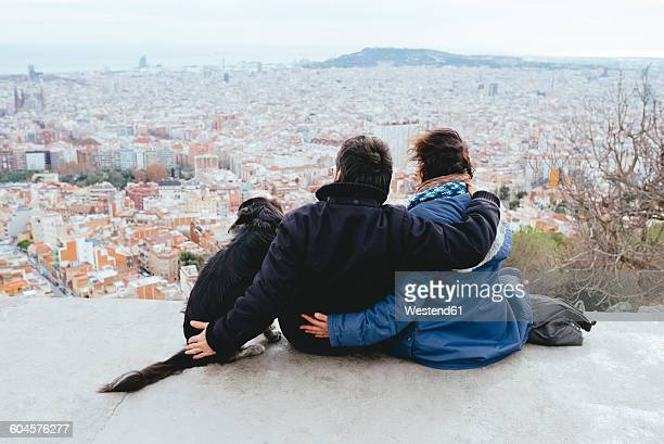 Spain, Barcelona, back view of couple with dog looking at view from Turo de la Rovira
