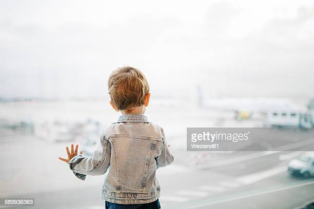 spain, barcelona, back view of little boy looking through window at the airport - toddler at airport stock pictures, royalty-free photos & images