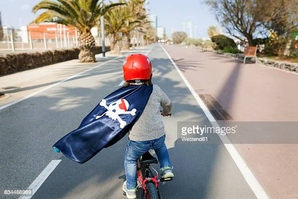 spain, barcelona, back view of little boy with a pirate cape riding bicycle on an empty street - velo humour photos et images de collection