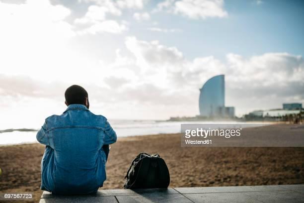 spain, barcelona, back view of young traveler sitting at the beach - hombre de espaldas playa fotografías e imágenes de stock