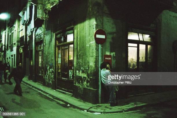 Spain, Barcelona, Barrio Chino, man leaning on wall at street corner