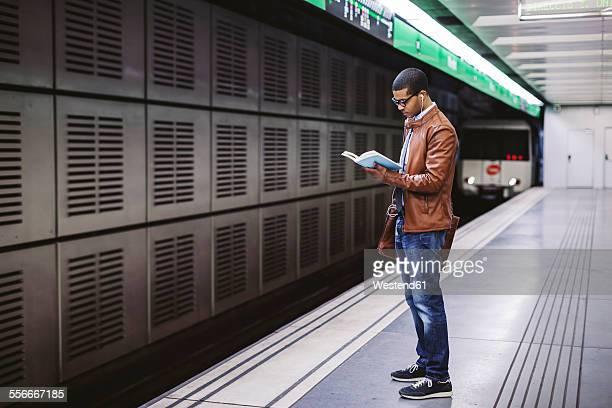 Spain, Barcelona, businessman standing at underground station platform reading book