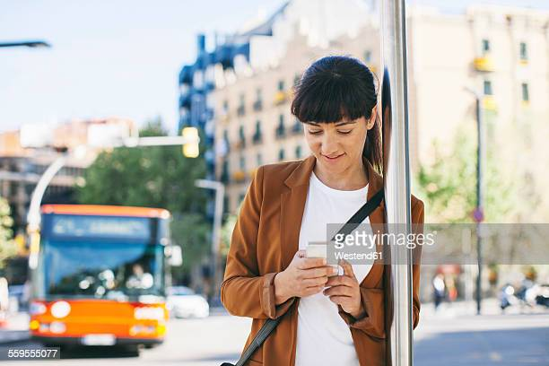 Spain, Barcelona, businesswoman with smartphone waiting at the bus stop