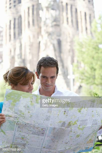 Spain, Barcelona, couple reading map near Sagrada Familia, close-up