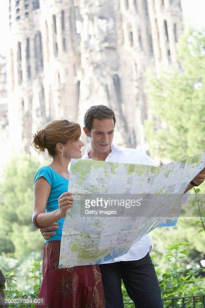 Spain, Barcelona, couple reading map near Sagrada Familia