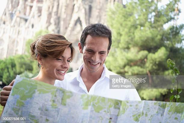 Spain, Barcelona, couple reading map near Sagrada Familia, smiling
