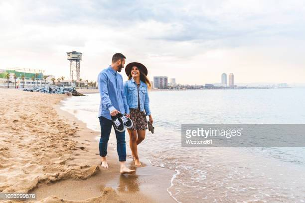spain, barcelona, couple walking barefoot on the beach - tourist fotografías e imágenes de stock