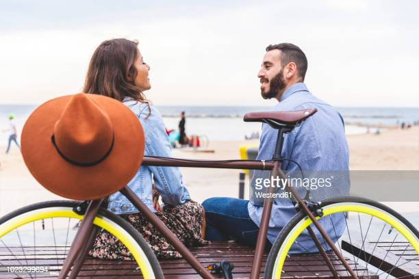 spain, barcelona, couple with bicycle sitting at the seaside - panchina foto e immagini stock