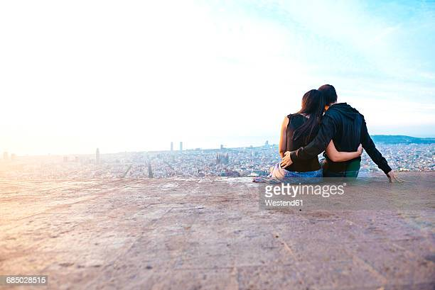 Spain, Barcelona, Embracing couple looking at view over city