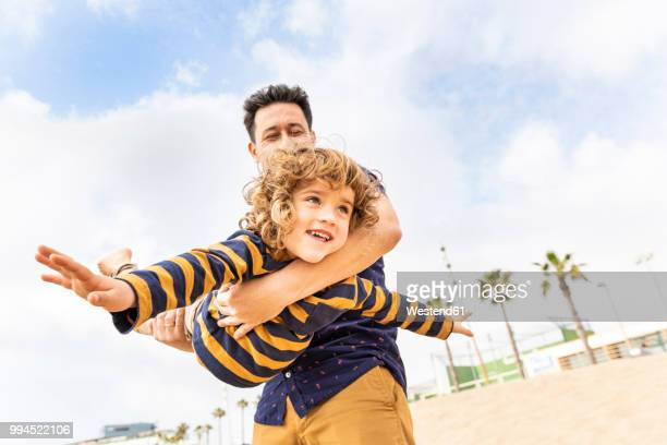 Spain, Barcelona, father and son playing on the beach