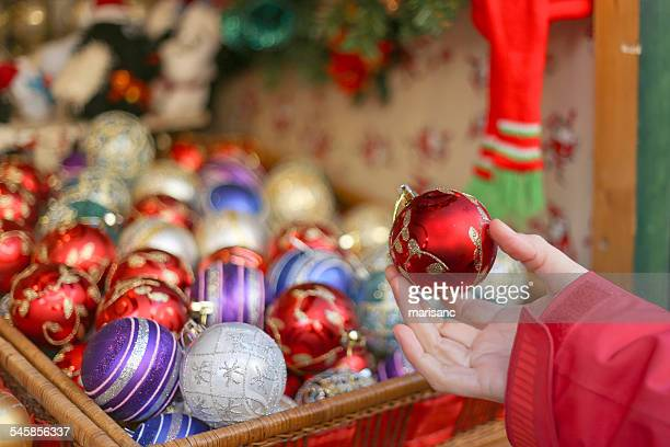 spain, barcelona, fira de santa lucia, hand holding red christmas bauble with other baubles in background - fira de barcelona stock pictures, royalty-free photos & images