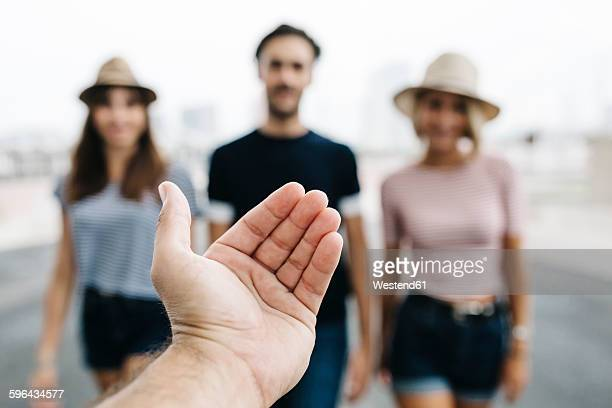 Spain, Barcelona, gesture of man's hand with three friends standing in the background