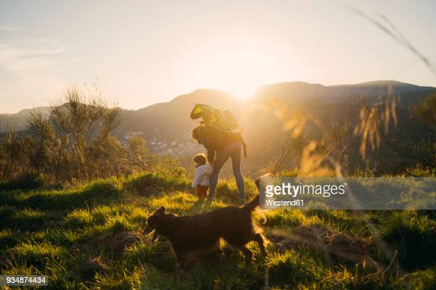 Spain, Barcelona, grandmother with granddaughter and dog during a hike at sunset
