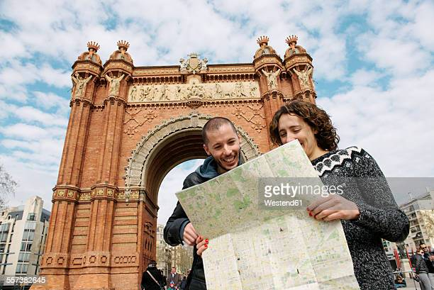 Spain, Barcelona, happy couple watching city map in front of trymphal arch