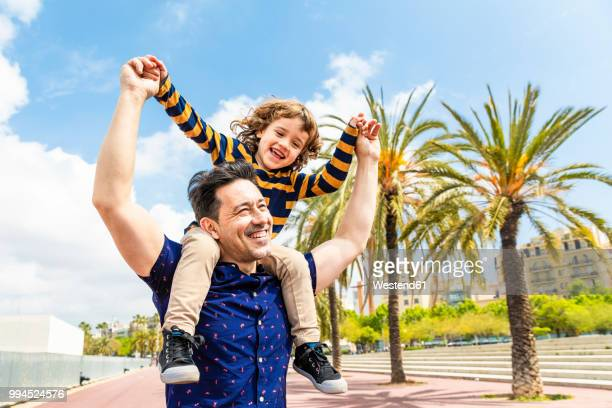 spain, barcelona, happy father carrying son on shoulders - genderblend stock pictures, royalty-free photos & images