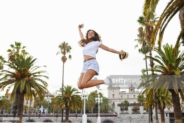 spain, barcelona, happy woman jumping mid-air surrounded by palm trees - pantalón corto fotografías e imágenes de stock