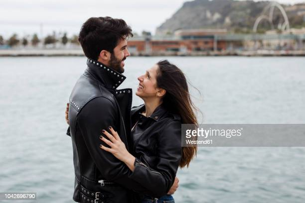Spain, Barcelona, happy young couple hugging at the coast