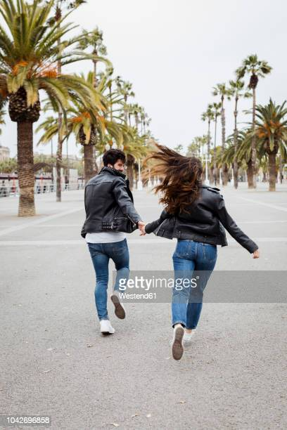 spain, barcelona, happy young couple running on promenade with palms - blouson en cuir photos et images de collection