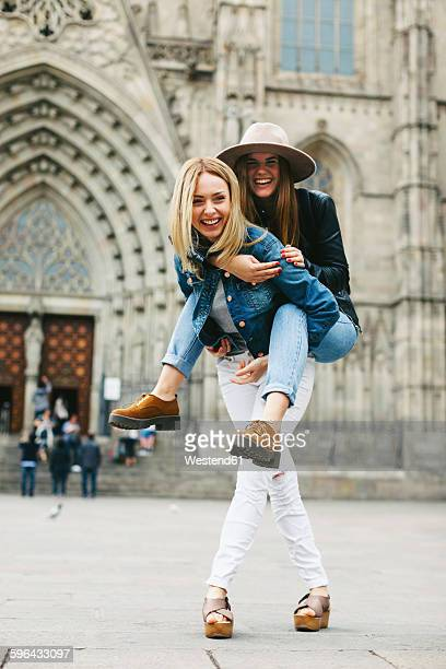 Spain, Barcelona, happy young woman carrying friend piggyback in the city