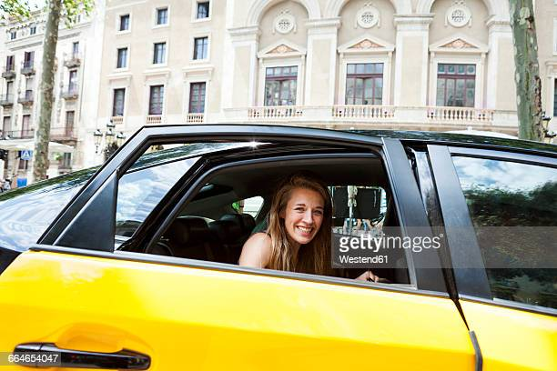 Spain, Barcelona, happy young woman looking out of taxi cab window