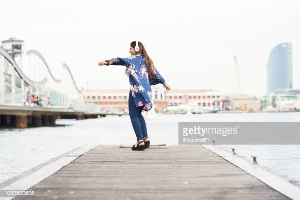 spain, barcelona, happy young woman with headphones dancing on jetty - incidental people stock pictures, royalty-free photos & images