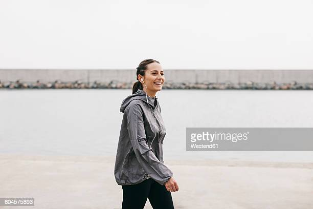 Spain, Barcelona, jogging woman with headphones at harbour