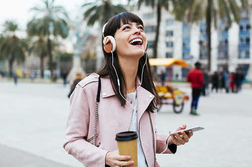 Spain, Barcelona, laughing woman with coffee, cell phone and headphones in the city - gettyimageskorea