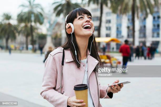 spain, barcelona, laughing woman with coffee, cell phone and headphones in the city - luisteren stockfoto's en -beelden