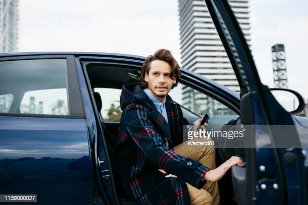 spain, barcelona, man getting out of the car with cell phone in his hand - leaving stockfoto's en -beelden