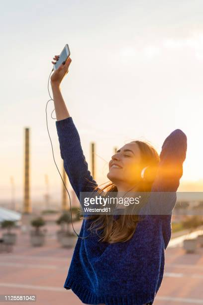 spain, barcelona, montjuic, happy young woman listening to music with headphones at sunset - twilight stock pictures, royalty-free photos & images