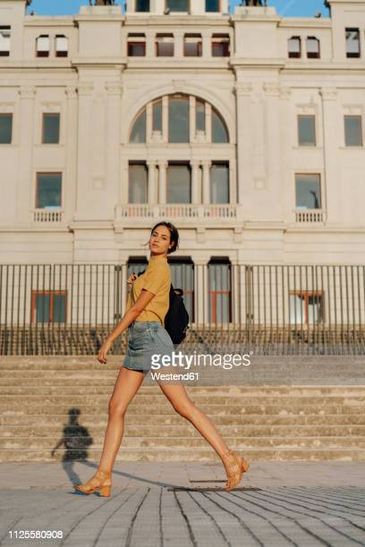 spain, barcelona, montjuic, portrait of young woman passing a building - minirok stockfoto's en -beelden