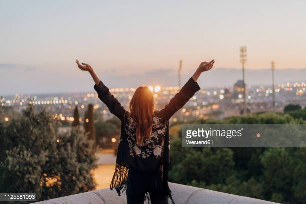 spain, barcelona, montjuic, rear view of young woman with raised arms with city lights in background - physical description stock pictures, royalty-free photos & images
