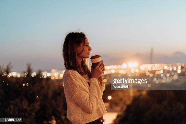 spain, barcelona, montjuic, young woman holding takeaway drink at dusk with city lights in background - hot spanish women stock pictures, royalty-free photos & images